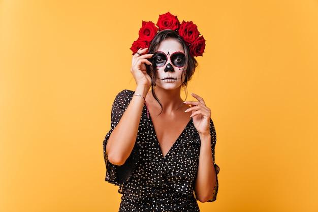 꽃의 왕관과 해골 마스크가있는 어두운 피부의 소녀가 할로윈을 기념하여 사진을 찍습니다. 특이한 복장에 특별한 모델의 초상화