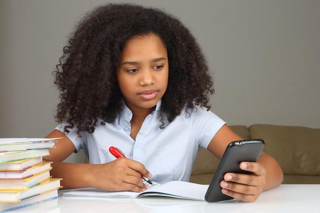 Темнокожая девушка со смартфоном делает домашнее задание