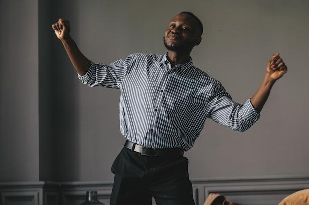 회색 배경에 어두운 피부를 가진 남자는 훌륭한 음악을 춤을 춥니 다.