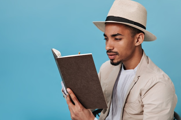 Dark-skinned guy with hat stares intently into his notebook