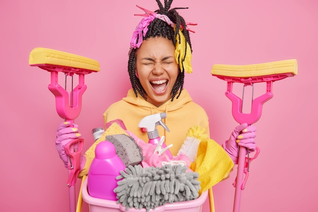 Dark skinned housewife exclaims loudly holds two mops