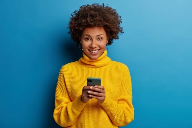 어두운 피부의 여인은 먼 의사 소통을 즐기고 휴대 전화를 사용합니다.