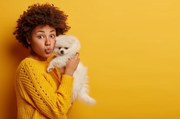 La signora dalla pelle scura mantiene le labbra arrotondate, vuole baciare adorabili animali domestici, gioca con un piccolo cucciolo Foto Gratuite