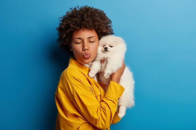 La signora dalla pelle scura mantiene le labbra arrotondate, vuole baciare adorabili animali domestici, gioca con un piccolo cucciolo
