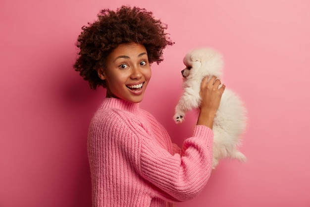 Dark skinned lady keeps lips rounded, wants to kiss adorable pet, plays with small puppy