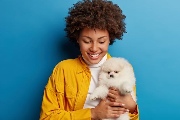 어두운 피부의 숙녀는 입술을 둥글게 유지하고 사랑스러운 애완 동물에게 키스하고 싶어하며 작은 강아지와 놀아요.
