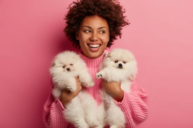 Темнокожая дама держит губы округлыми, хочет поцеловать очаровательного питомца, играет с маленьким щенком