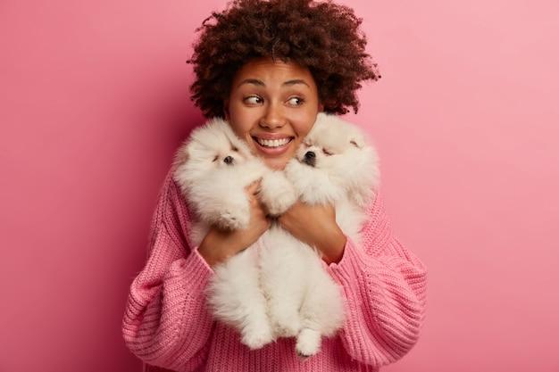 浅黒い肌の女性は唇を丸く保ち、愛らしいペットにキスしたい、小さな子犬と遊ぶ