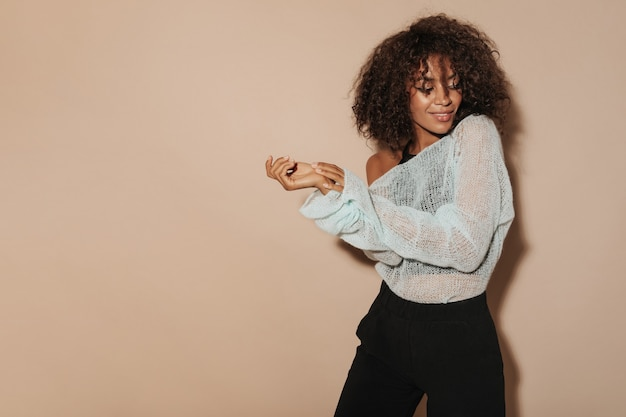 明るいセーターと黒のクールなズボンで短いふわふわの髪型を持つ暗い肌の女性は、孤立したベージュの壁に微笑んでいます。