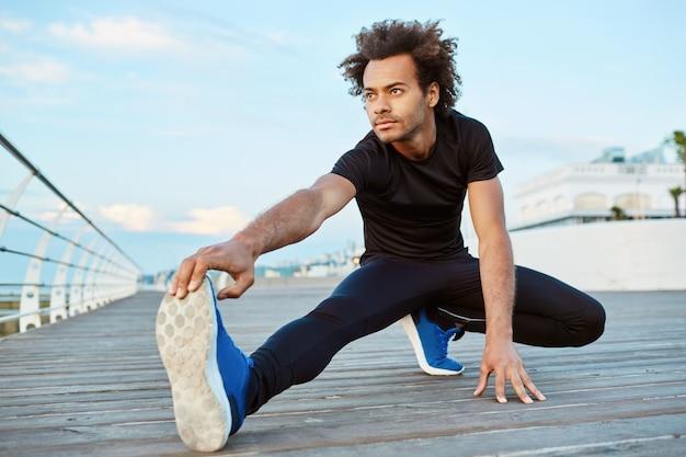 Темнокожий спортсмен-мужчина с густыми волосами делает упражнения и растягивает ноги.