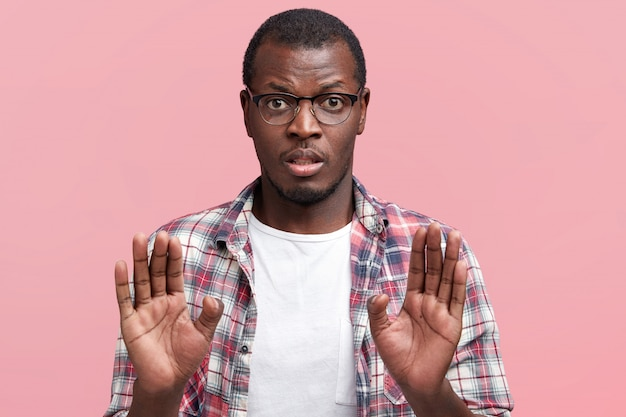 Dark skinned male in eyewear refuses to do something, keeps palms in foreground, denies or rejects to go somewhere, wears spectacles and checkered shirt, isolated over pink