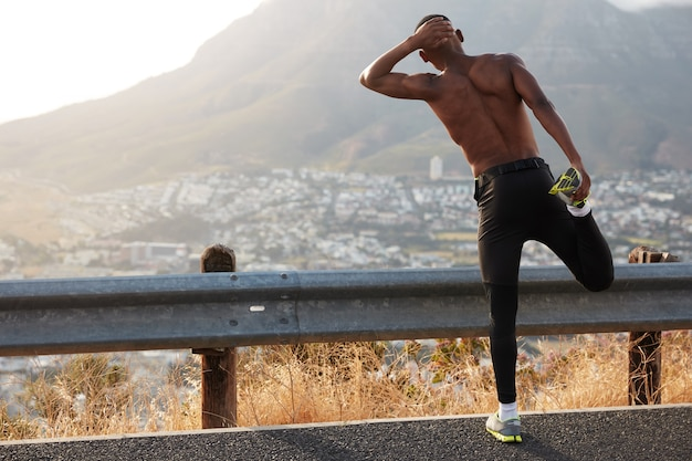 Dark skinned male stands back, makes stretching exercises, raises legs, admires beautiful mountain view, has workout training, wears sneakers, stands on asphalt. wellness and fitness