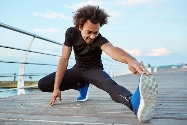 검은 색 운동복과 파란색 운동화를 입은 어두운 피부의 남자 선수가 부두에서 런지 햄스트링 스트레칭 운동으로 다리를 뻗고 있습니다. 아프리카 계 미국 흑인 젊은 남성 러너 워밍업