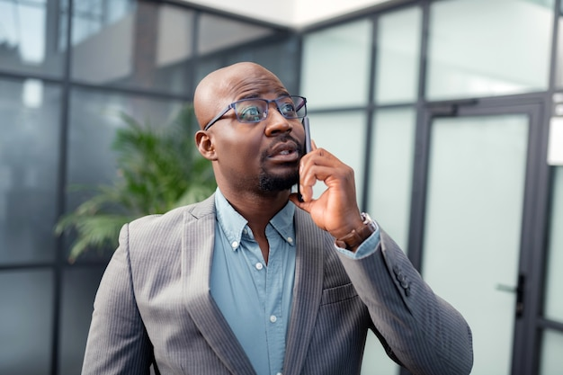 浅黒い肌の男。オフィスからビジネスパートナーを呼び出す眼鏡をかけている浅黒い肌のひげを生やした男