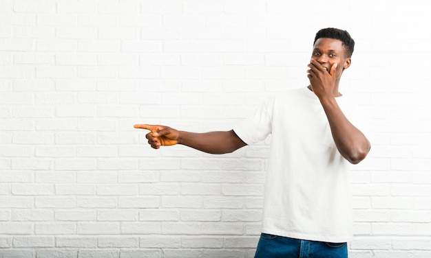 Dark skinned man pointing finger to the side and presenting a product with a surprised face