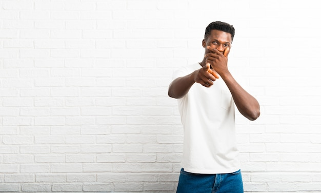 Dark skinned man pointing with finger at someone and laughing a lot while covering mouth