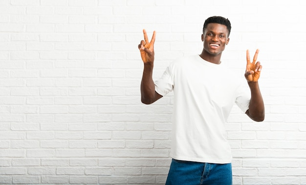 Dark skinned man smiling and showing victory sign with both hands and with a cheerful face