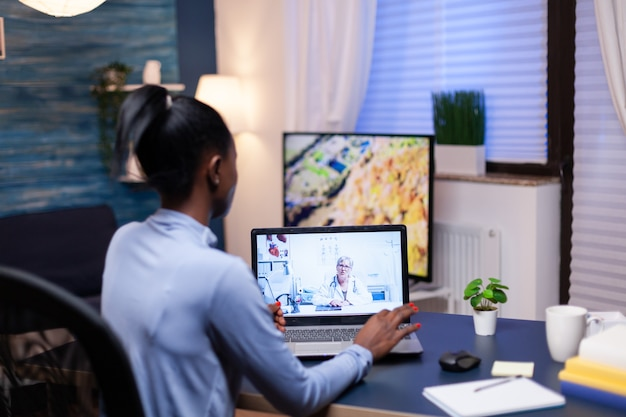 Dark skinned patient talking with doctor in the course of video conference from late at night. woman discussing during virtual consultation about symptoms.