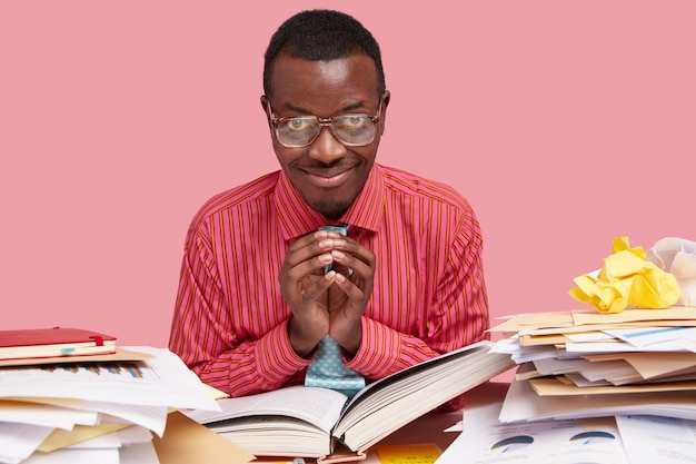 Lo studente universitario afroamericano dalla pelle scura tiene la mano in un gesto intrigante, ha una bella idea da esprimere, legge un libro spesso