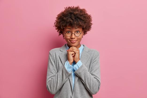 Bella donna dalla pelle scura in occhiali con acconciatura riccia tiene le mani sotto il mento, ascolta attentamente