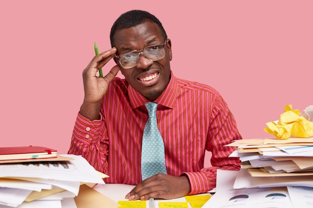 Dark skinned professional male editor prepares article for newspaper, works with documents, pretends smiling, holds pen for writing