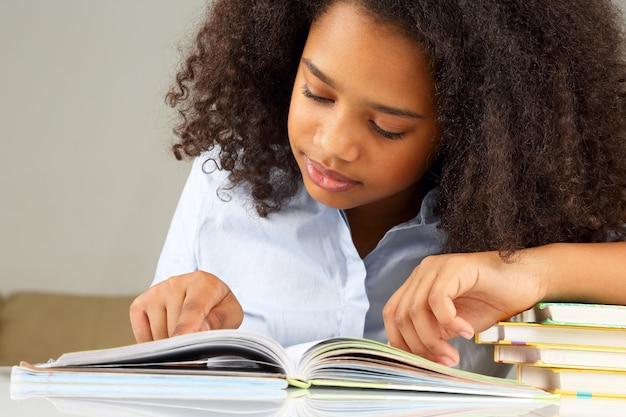 숙제를 하 고 책을 읽고 어두운 피부여 학생