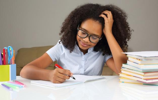 宿題をしている眼鏡をかけた浅黒い肌の女子高生
