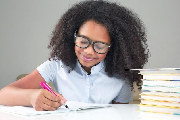Dark-skinned schoolgirl with glasses writes in a notebook. learning in school education