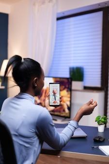 オンライン相談の過程で医師と話し合っている浅黒い肌の病気の女性。女性の健康問題について話し合うメディックとのビデオ通話中の黒人患者。