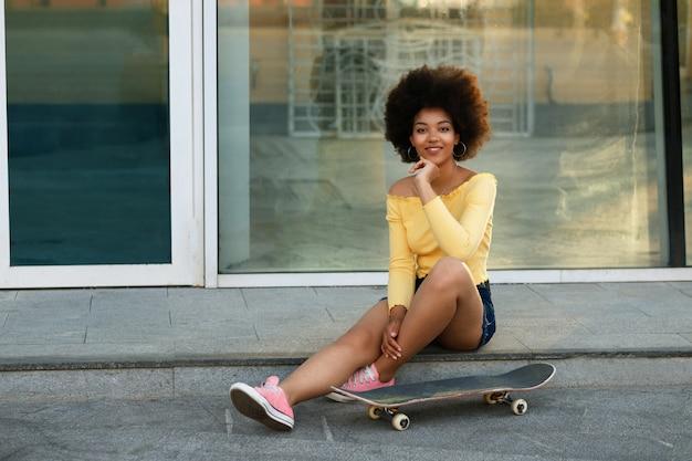 Темнокожий скейтбордист летом отдыхает на прогулке