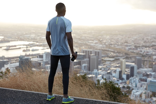 Dark skinned sportsman in sportswear, stands back, drinks water from bottle, wears sneakers, stands high and enjoys scenic city view with sky scrapers from above, has outdoor workout in countryside