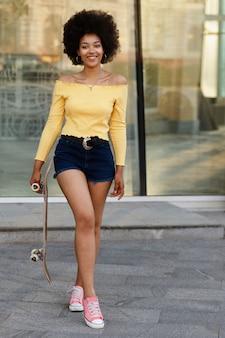 Темнокожая студентка с скейтбордом на прогулке летом
