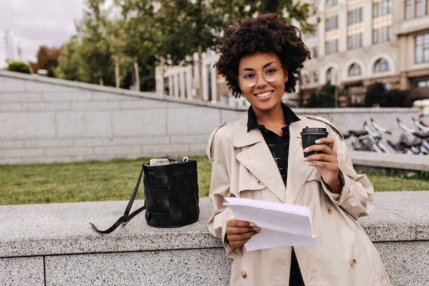 Dark-skinned stylish woman in eyeglasses holds coffee cup and paper sheet