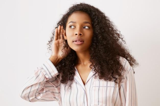Adolescente dalla pelle scura in pigiama tenendosi per mano all'orecchio, origliando. femmina abbastanza afroamericana che ha uno sguardo curioso, ascoltando una conversazione segreta interessante, tenendo la bocca aperta