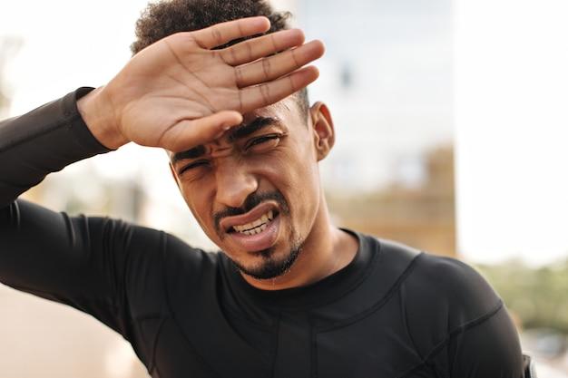 浅黒い肌の疲れたブルネットの男が顔に触れる