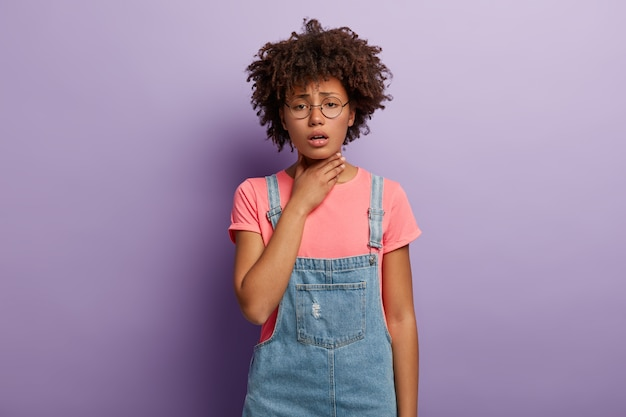 Dark skinned unhappy woman holds inflamed throat, feels pain while swallows, has cough, dressed in stylish clothes, spectacles isolated over purple wall. bad symptoms. problems with health