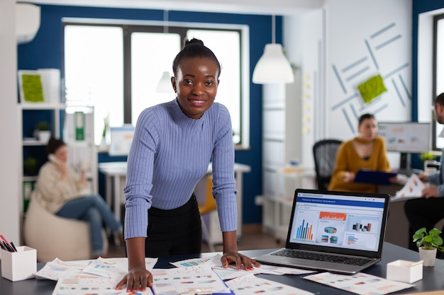 Dark skinned woman and colleagues in corporate start up office working to finish project. diverse team of business people analyzing company financial reports from computer.