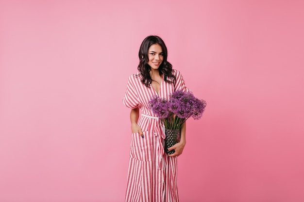 Dark-skinned woman confidently in pink room. lady in long sundress holds vase of flowers.