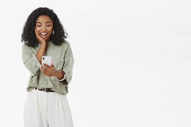 Темнокожая женщина, глядя на смартфон