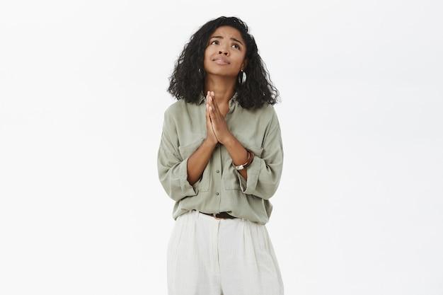 Donna dalla pelle scura che si tiene per mano in preghiera che osserva in su con sguardo fedele triste che fa desiderio