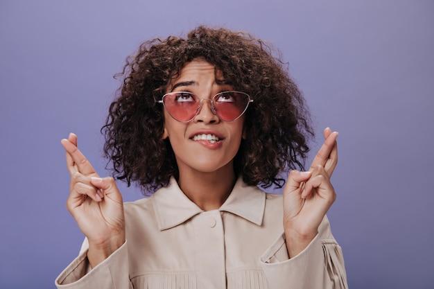 眼鏡をかけた浅黒い肌の女性が見上げて指を交差させる