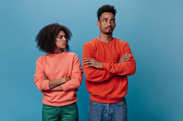 Dark skinned woman and man in orange sweatshirts are sad and posing on blue wall