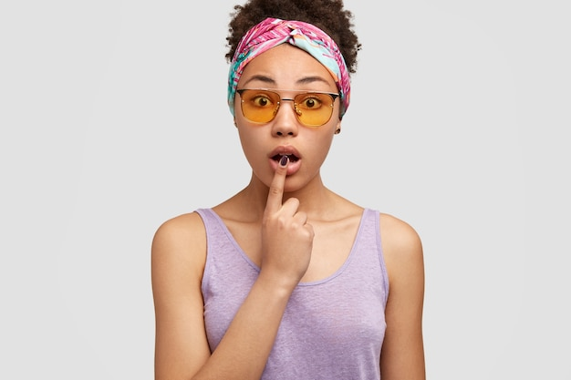 Dark skinned woman opens mouth, keeps fore finger at lip, has fascinated facial expression, shocked with astonishing news, wears trendy sunglasses, models over white wall