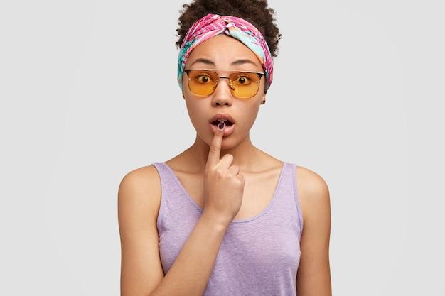 Una donna dalla pelle scura apre la bocca, tiene l'indice sul labbro, ha affascinato l'espressione del viso, scioccata da notizie sorprendenti, indossa occhiali da sole alla moda, modelle sul muro bianco
