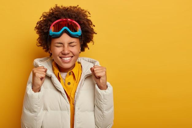 Una donna dalla pelle scura alza i pugni chiusi, sorride e sorride allegramente, indossa una maschera da snowboard, cappotto invernale