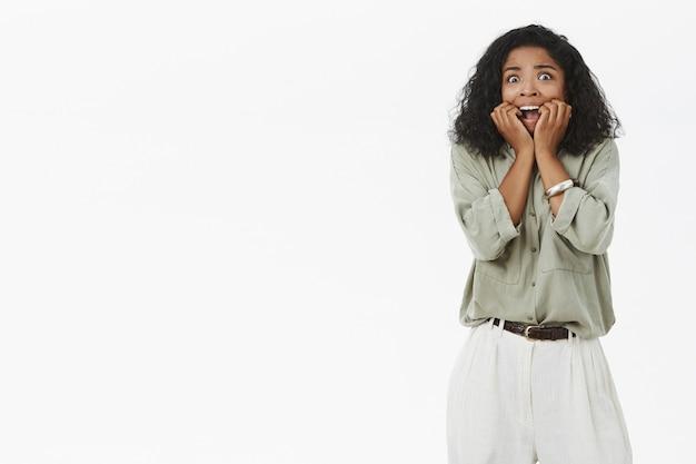 Темнокожая женщина кричит от испуга, держа пальцы во рту