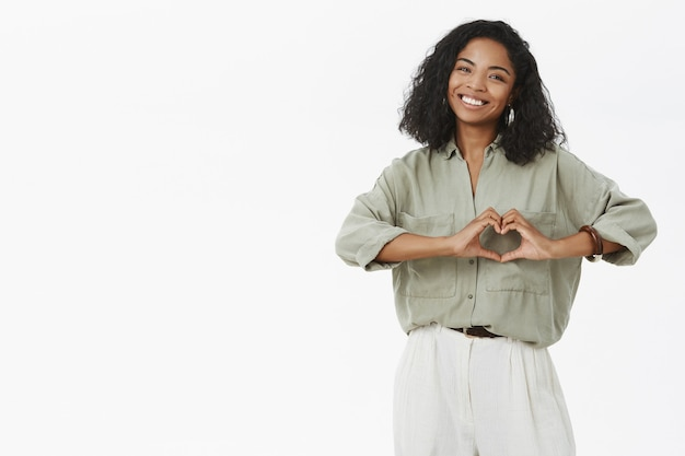 Dark skinned woman  showing heart gesture over chest