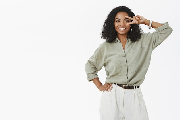Dark skinned woman  showing peace gesture near face holding hand on hip and smiling joyfully