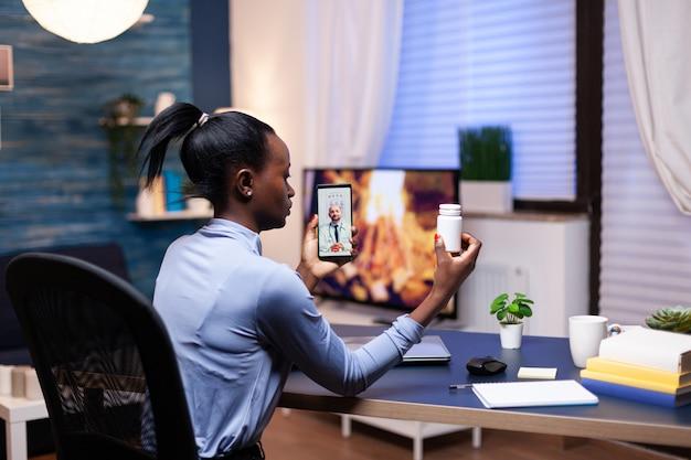居間から深夜のビデオ通話中に医者に薬瓶を見せている暗い肌の女性。女性の健康問題について話し合うメディックとのビデオ通話中の黒人患者。