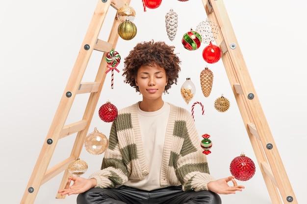 Темнокожая женщина сидит в позе лотоса, держит глаза закрытыми, глубоко дышит, выполняет медитационные упражнения, пытается расслабиться в позах спокойной атмосферы.